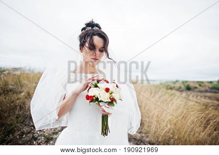 Lonely Beautiful Bride In The Middle Of Breathtaking Landscape With A Bouquet On A Day Of Her Weddin