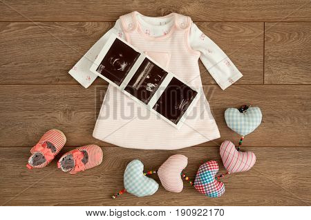 Flat lay of little pink dress and tiny shoes of infant baby girl along with sonography pictures and colorful cotton hearts on brown wooden surface with copy space.
