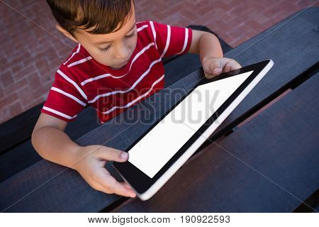 High angle view of boy using tablet while sitting at table in school