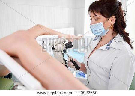 Female gynecologist working at the hospital examining her patient on a gynecological chair profession job occupation medicine clinical healthcare feminine concept.