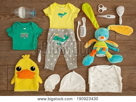 Essential accessories of a newborn infant shot from above in a tabletop flat lay arrangement on brown wooden surface.