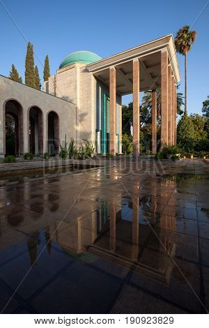 Mausoleum of Saadi the famous Persian poet and its reflection on wet floor shot after a shower rain on a sunny day in Shiraz city of Iran.
