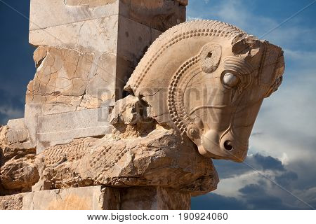Ornamental bull statue from Achaemenid dynasty used as a column capital in Persepolis of Shiraz city in Iran Against Cloudy Blue Sky.