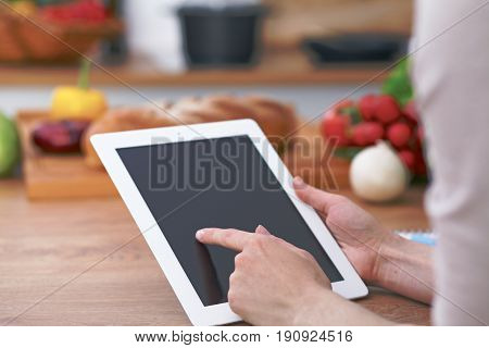 Close-up of human hands are gesticulate over a tablet in the kitchen. Women choosing menu or making online shopping. So much ideas for tasty cooking. Vegetarian, healthy meal and friendship concept.