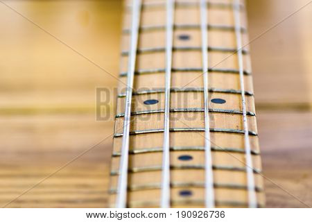 closeup of electrical bass guitar fingerboard defocused deep of field wooden background