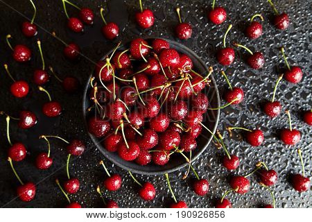 Sweet cherry in a black plate on a black table with drops of water on the surface of the berry and background. View from above. Antioxidant, natural, vitamin, organic berry. Flat lay.