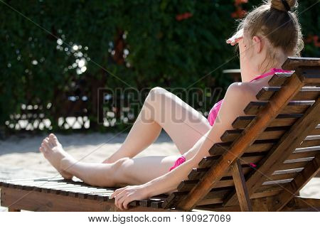Girl in a swimsuit on a deckchair in the backyard
