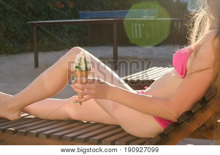 Girl on deckchair with ice cream in hand body part