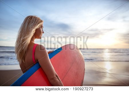 Beautiful woman with surfboard outdoors