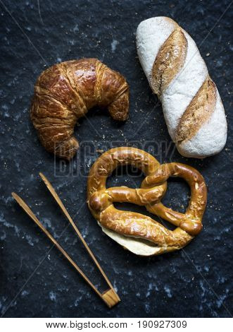 Croissant pretzel and baguette with wooden tongs