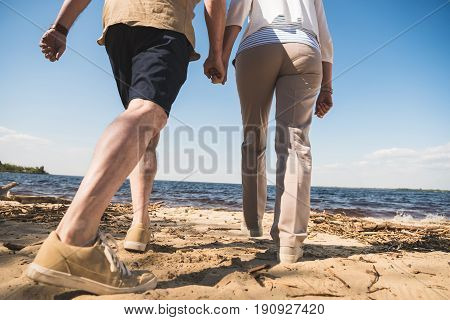Cropped shot of senior couple holding hands and walking on sandy beach