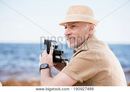 Smiling Senior Man In Hat Holding Instant Camera And Looking Away Outdoors