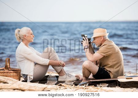 Side View Of Senior Man In Hat Photographing Smiling Woman With Instant Camera At Beach