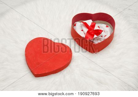 Open red box with heart shaped linen white fur. Top view