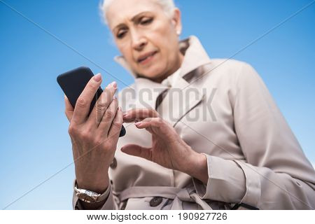 pensive grey haired woman using smartphone outdoors