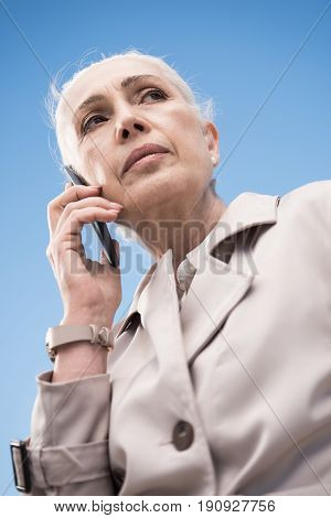 pensive grey haired woman talking on smartphone outdoors