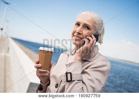 smiling elderly woman talking on smartphone and holding coffee cup at quay