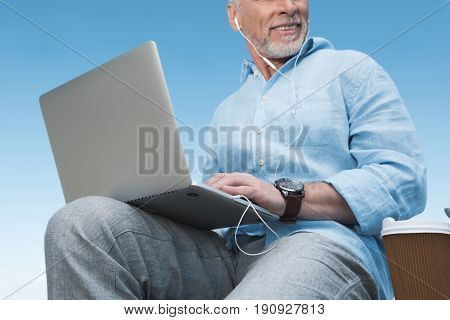 Senior Man Working On Laptop And Listening Music In Earpods Outdoors