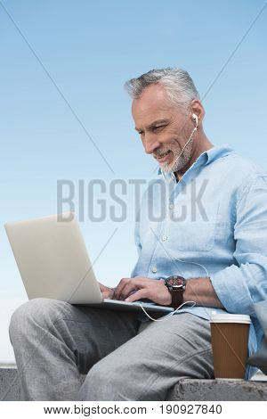 Smiling Senior Man Typing On Laptop And Listening Music In Earpods Outdoors