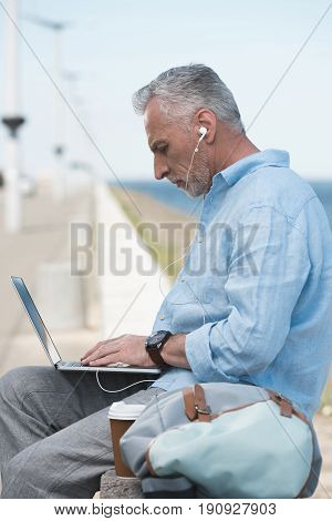 Casual Elderly Man Typing On Laptop And Listening Music In Earpods Outdoors