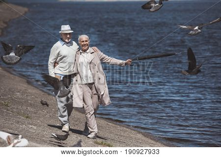 Smiling Elderly Couple Walking On River Shore At Daytime