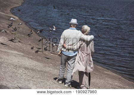 Casual Senior Couple Walking On River Shore At Daytime