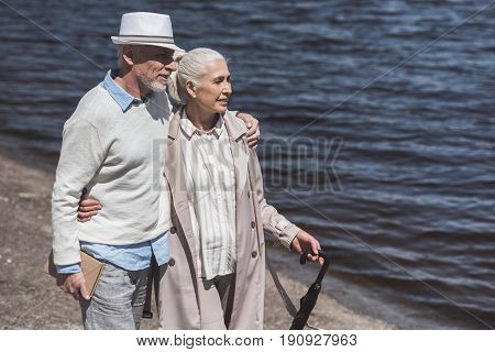 Casual Grey Haired Couple Walking On Riverside At Daytime