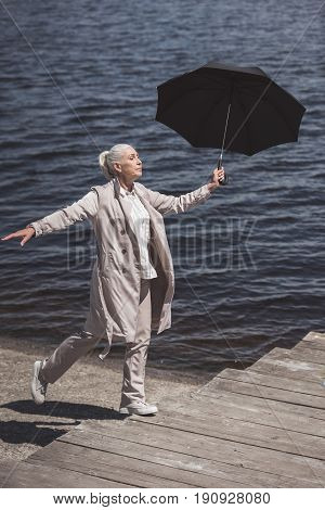 Casual Elderly Woman Walking With Umbrella On Riverside At Daytime