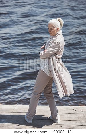 Casual Elderly Woman Posing With Arms Crossed On Riverside At Daytime