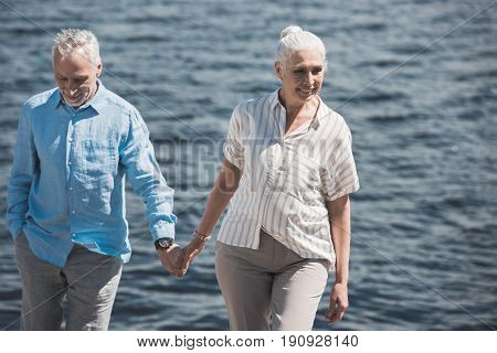 Smiling Elderly Couple Holding Hands And Walking On Riverside At Sunny Day