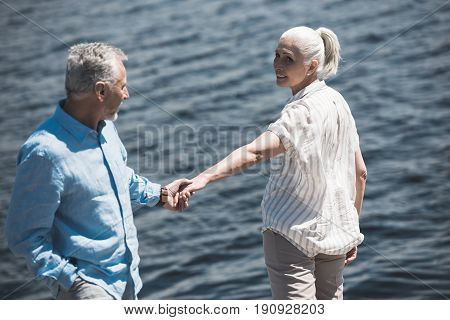 Casual Elderly Couple Holding Hands On Riverside At Daytime