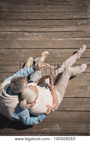 Above View Of Senior Couple Reading Book While Sitting On Wooden Pavement