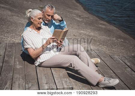 Elderly Couple Reading Book While Resting On The Quay At Daytime