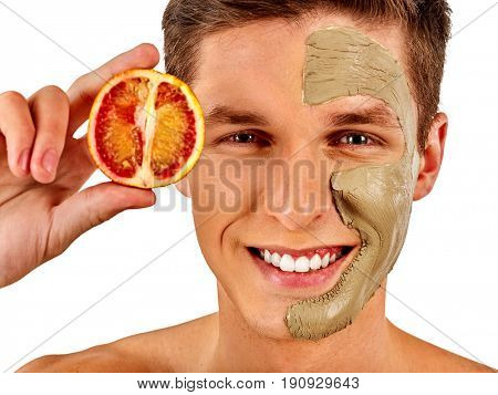 Facial mask from fresh fruits and clay for man concept. Face with treatment mud applied. Male holding lemon half for skin care procedure in salon. Man smiles dazzlingly on isolated.