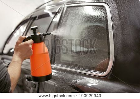 Worker spraying water onto car window prior to tinting