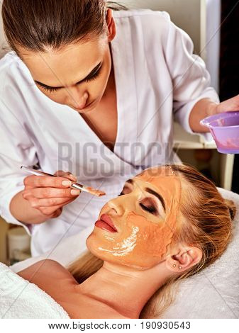 Collagen face mask. Facial skin treatment. Woman receiving cosmetic procedure in beauty salon. Bottle with moisturizing cream on background. Mask against black dots.