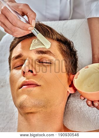 Mud facial mask of man in spa salon. Massage with clay full face. Man lying on spa bed. Beautician with bowl therapeutic procedure isolated background. Home cosmetics with egg yolk.