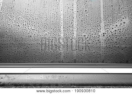 Drops on wet tinted car window, closeup