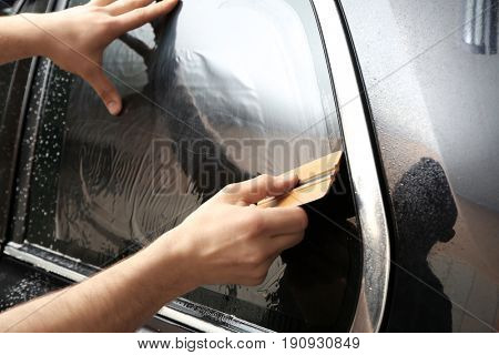 Worker installing tinting foil on car window