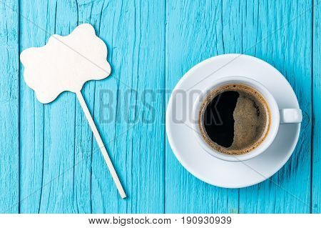 Cup of coffee with empty topper for wishes on blue wooden table