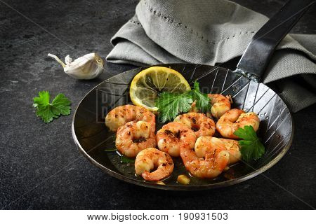 Prawns Shrimps With Garlic, Lemon, Spices And Italian Parsley Garnish In A Black Pan On A Dark Slate
