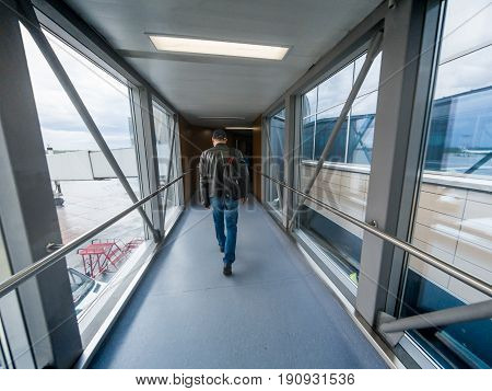 Man boarding in airport gate or jet bridge or jetway or airbridge to a plane, tunel vision, perspective