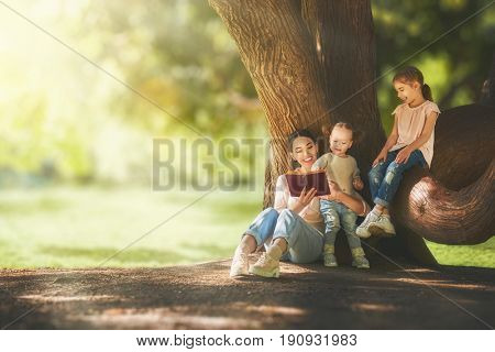 Mother and daughters sitting under the tree on summer lawn. Happy family playing outdoors. Pretty young mom reading a book to her children in the park outside.