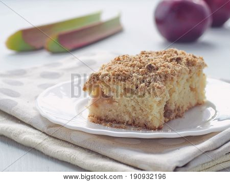 Coffee cake decorated with streusel and fresh rhubarb stems. Homemade apple pudding. Selective focus.