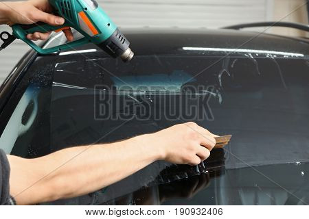 Worker applying tinting foil onto car window