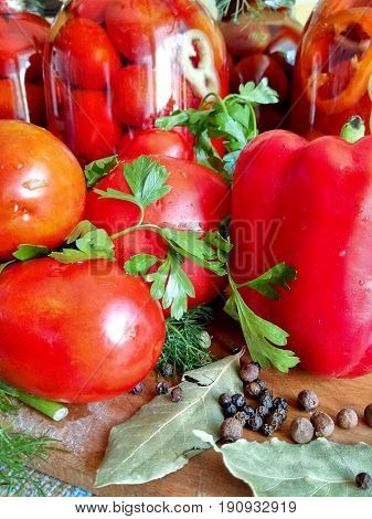 Home canning for the winter glass jars with red tomatoes and greens