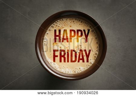 Text HAPPY FRIDAY and cup of coffee on gray background