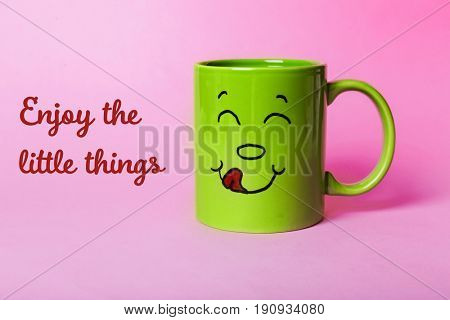 Text ENJOY THE LITTLE THINGS and cup with funny face on color background