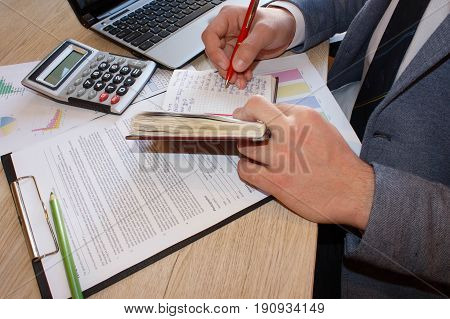 Working moments. Young man writing in his notebook while sitting at his working place in front of window. People writing on notebook and work with calculator and laptop on wooden table