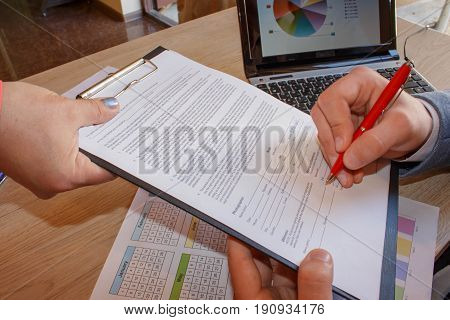 Business and office concept - close up of businessman with papers. Conceptual image of a man signing a last will and testament document